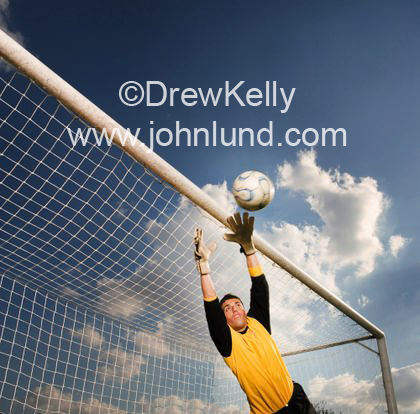 Sports stock photo of a soccer player in mid air blocking a goal attempt.